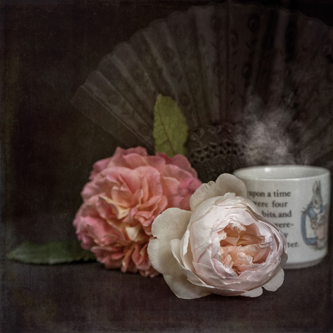 Still life photo-art of roses, a fan, and a steaming mug